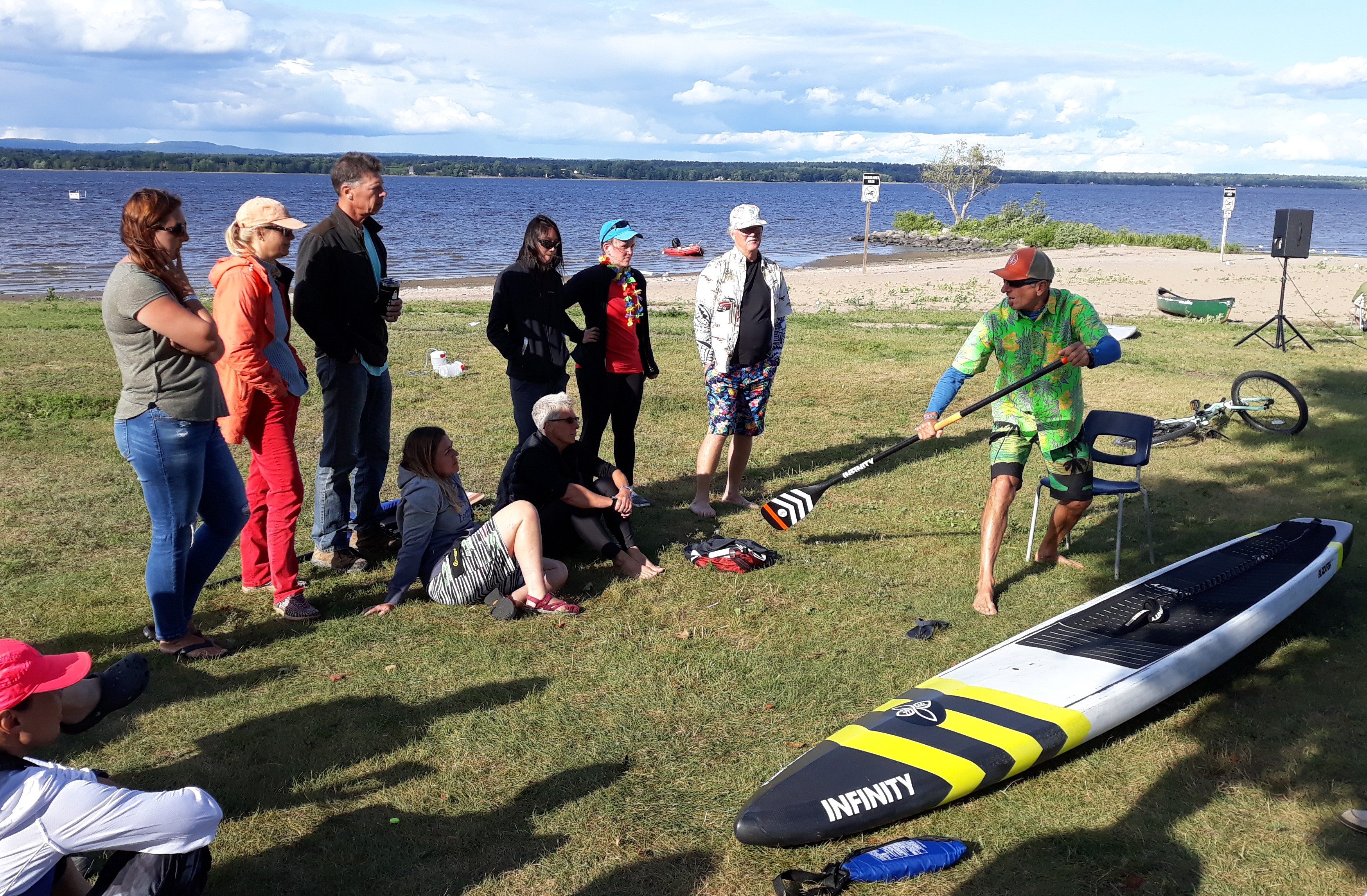 Image of instructor demonstrating SUO paddling technique to a group of participants