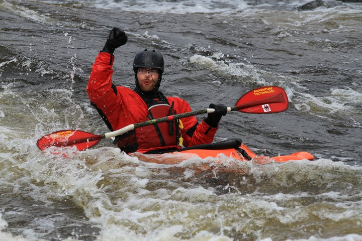 Image of kayaker in white water with fist pump in the air