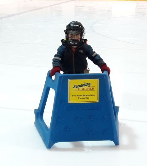 photo of young child using skating aid on ice