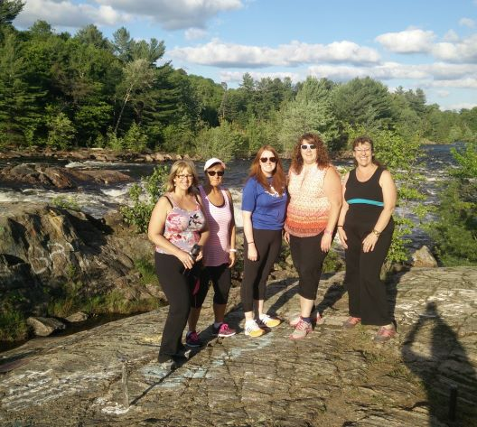 Image of 5 women from a hiking group with nature scene in background