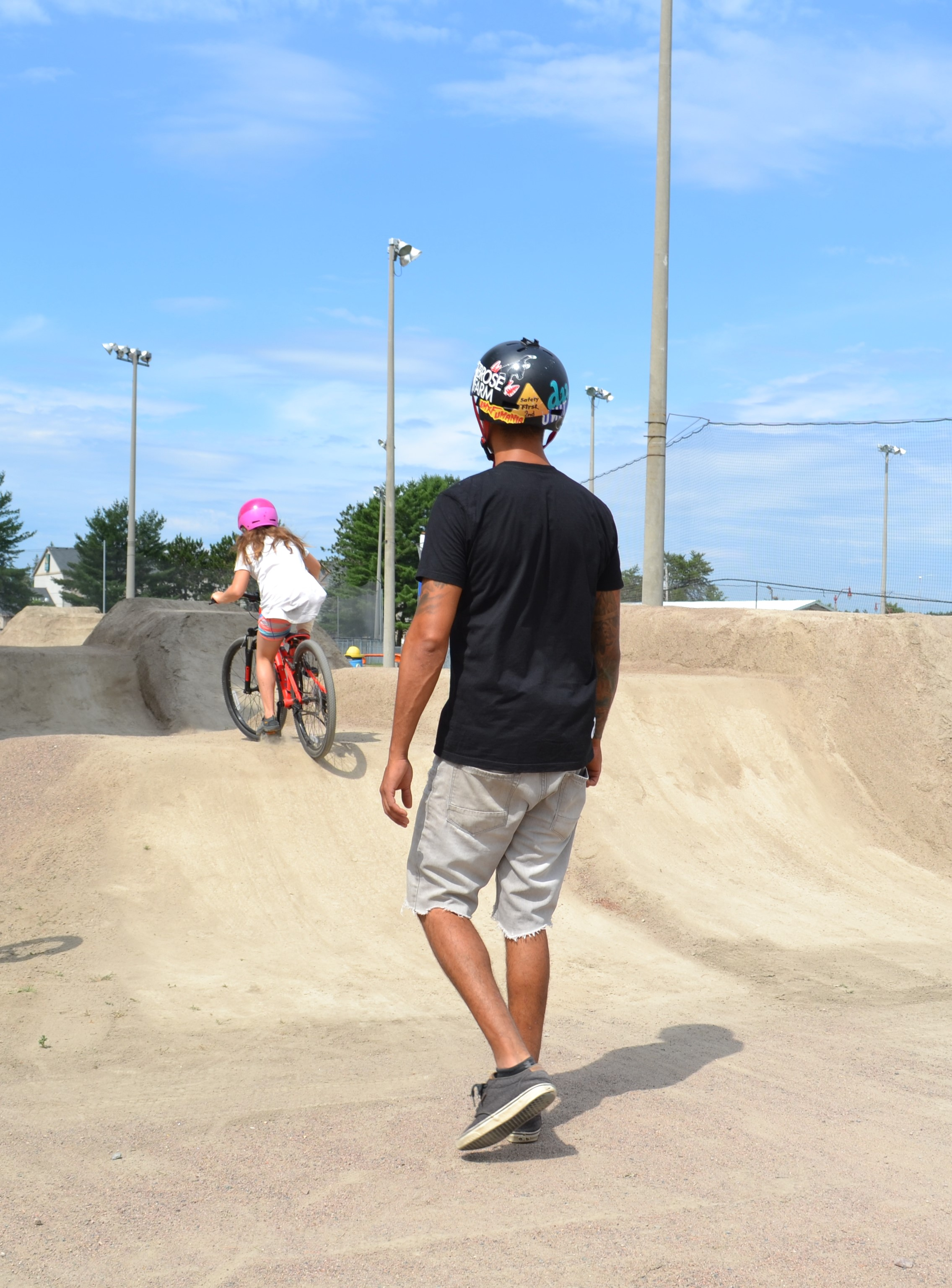 Image of adult supervising child on a jump in Bike Park