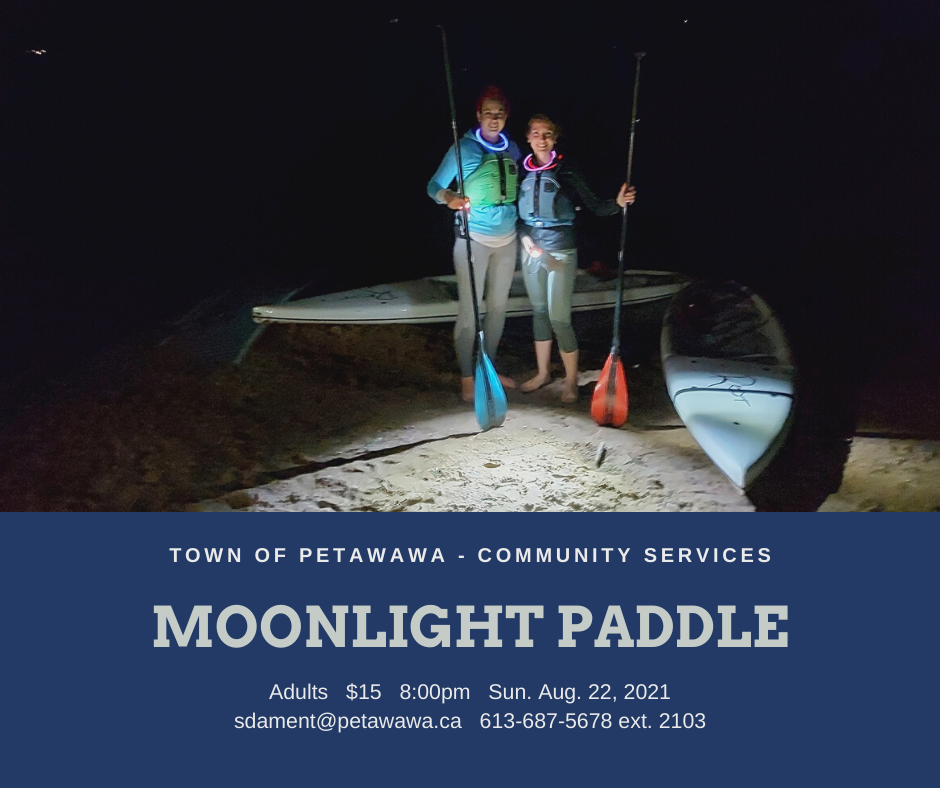 Two paddlers stand onshore by their paddleboards in the dark