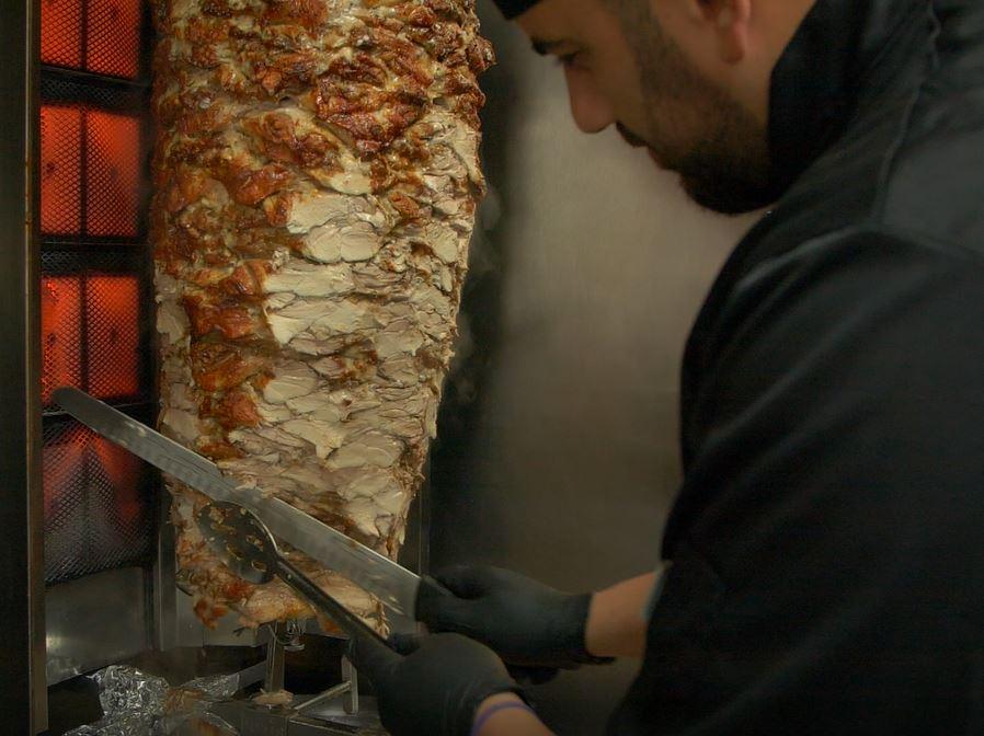 a shawarma in circulation being cut by a chef