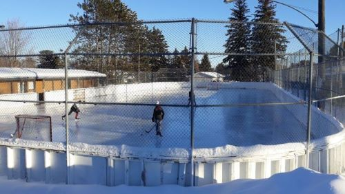 Photo of outdoor rink on a sunny day with 3 skaters