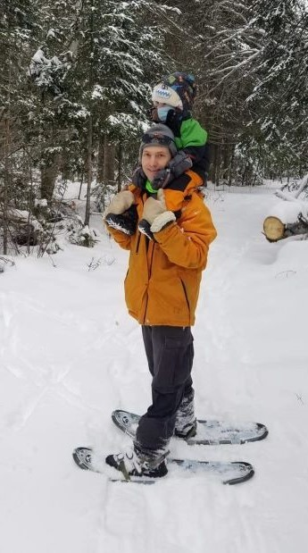 Image of father and toddler snowshoeing in a winter forest scene