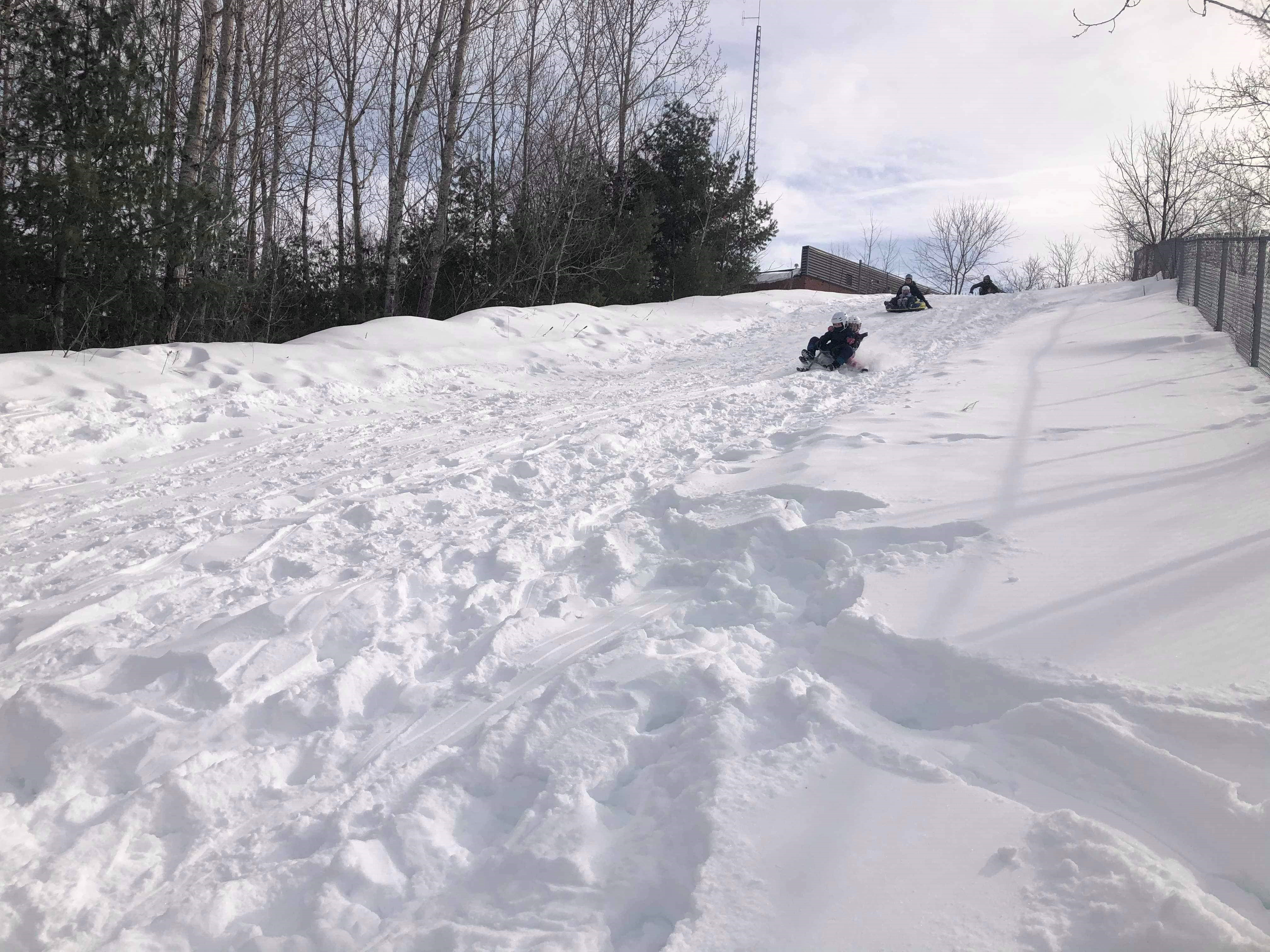 Image of 2 sledders coming down the snowy hill